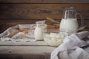 Fresh dairy products. Milk, cottage cheese, sour cream and wheat on rustic wooden background.