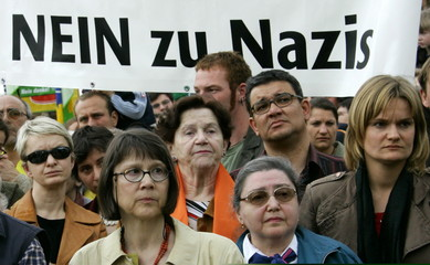 People gather in front of a banner which reads 'No to Nazis!' during a demonstration against racism ..