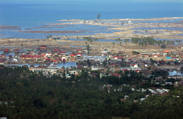 The tsunami-damaged area of Ulee Lheue is seen over the tsunami-hit city of Banda Aceh.