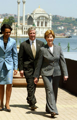 LAURA BUSH WALKS WITH MOSQUE IN BACKGROUND.