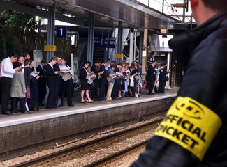 A striking member of the Rail, Maritime and Transport (RMT) Union (R) looks across at passengers wai..