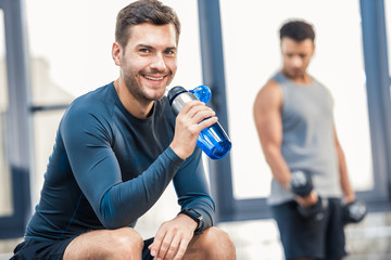 Handsome young man with bottle of water resting at gym, other man workout on blurred background