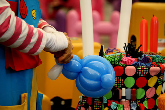 hand of balloon artist making balloon toy for kids