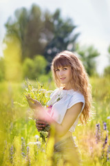 The beautiful young woman with a long fair hair holds a bouquet of wild flowers outdoors