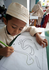 An Indonesian Muslim boy practises colouring Arabic letters during a morning class in Sukabumi