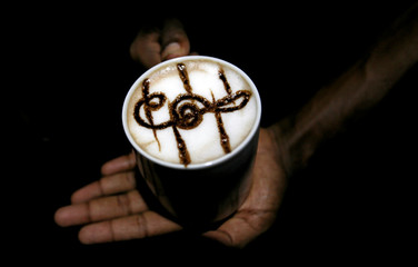 Barista holds cup of coffee with image of music symbol at Java Lounge coffee shop in Colombo