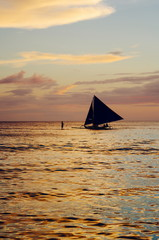 Beautiful colorful sunset over fishing boats and people in water