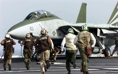 PERSONNEL RUN TO SECURE F-14 ABOARD USS KITTY HAWK OFF JAPAN.