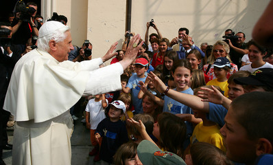 Pope Benedict XVI waves to a group of children upon his arrival for a meeting with priests in Introd.