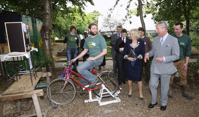 Britain's Prince Charles and his wife Camilla, Duchess of Cornwall laugh as they talk to a worker on a bike powering a DVD player in London