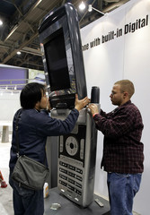 Workers set up cell phone for display at Consumer Electronics Show in Las Vegas.