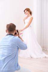 Wedding photographer taking photo of beautiful bride in studio