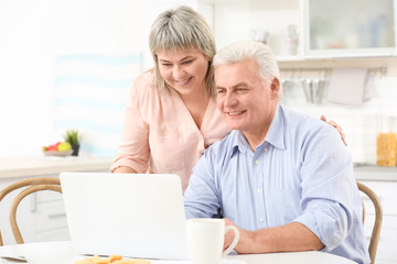 Middle aged couple with laptop at kitchen