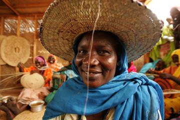 Women weave straw  baskets  at  ZamZam camp