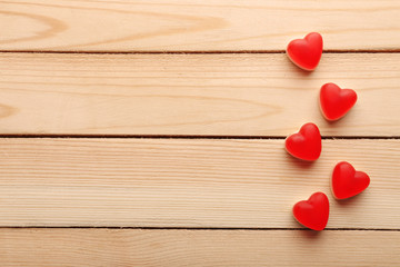 Tasty heart-shaped candies on wooden background