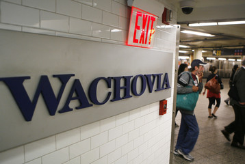 Commuters walk past a Wachovia Bank sign inside an ATM booth underneath Times Square in New York