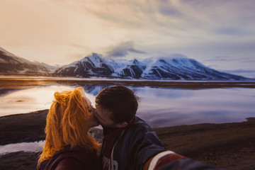 couple red-haired girl and man kissing on the background nature winter snow-capped mountains of Svalbard, Longyearbyen, Spitsbergen, Norway at the time of fire rolled reflection ocean wallpaper