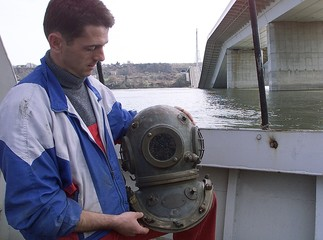 DIVER ADJUSTS HIS DIVING HELMET BESIDE DESTROYED BRIDGE OVER DANUBERIVER IN NOVI SAD.