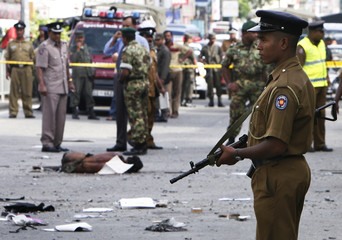 Police and military personnel investigate the site of a bomb explosion as a body lies on a street in Colombo