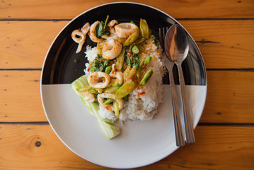 Rice topped with stir-fried squid and basil On the plate .