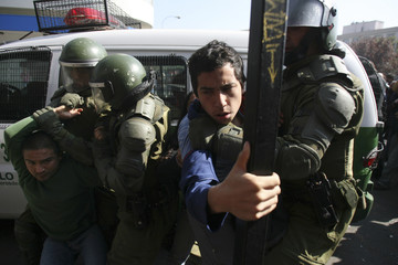 Riot police try to detain demonstrators during May Day rallies in Santiago