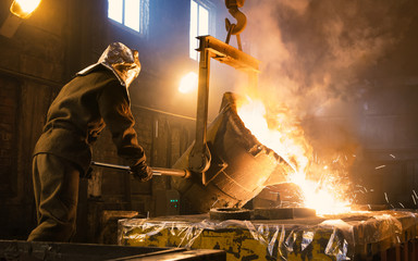 Worker controlling metal melting in furnaces. Workers operates at the metallurgical plant. The liquid metal is poured into molds.