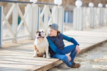 Nice looking handsome boy on beach with bulldog