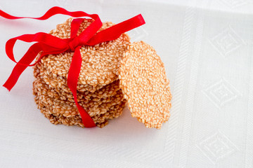 Sesame crisps tied red ribbon isolated on light background. Above