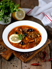 Traditional Russian soup solyanka made from cabbage, fresh and dried mushrooms with olives, lemon and capers.
