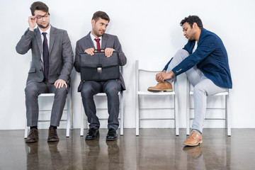 businessmen in suits sit on chairs at white waiting room. business meeting