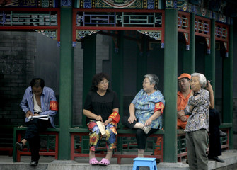Local elderly residents with red armbands chat by a street ahead of a rehearsal for the 60th anniversary of the founding of Communist China, in central Beijing