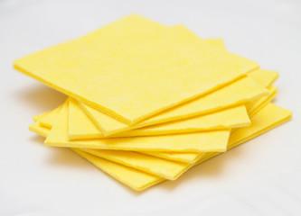 Vibrant yellow cloth kitchen napkins isolated on white.