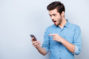 Surprised young man is holding phone and reading message pointing on it with finger