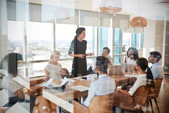 Businesswoman Leads Meeting Around Table Shot Through Door