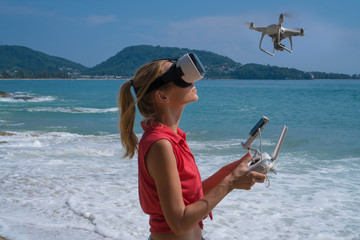 Pretty woman wearing virtual reality glasses standing on the beach with remote controller of drone over sea and sky background