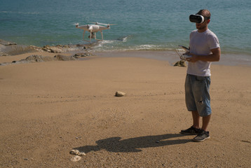 Young man wearing virtual reality glasses standing on the beach with remote controller of drone over sea and sky background