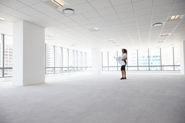 Female Architect In Modern Empty Office Looking At Plans
