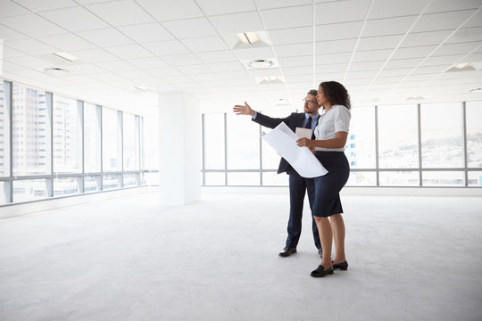 Businesspeople Meeting To Look At Plans In Empty Office
