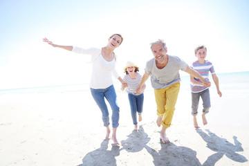 Happy family of four walking on sandy beach
