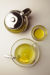 Herbal mint tea in a glass cup with lemon, the teapot and honey