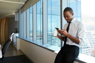 Man using phone while sitting onwindowsill