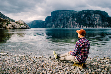 Lonely traveler tourist man resting on shore of fjord in Norway with  far view of water and mountains valley at horizon in summer cloudy day. Contemplation. Reflection. Holidays. Vacation. Nature.