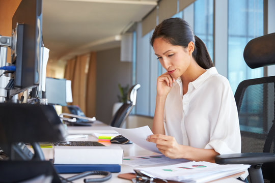 Businesswoman At Office Desk Reading Document