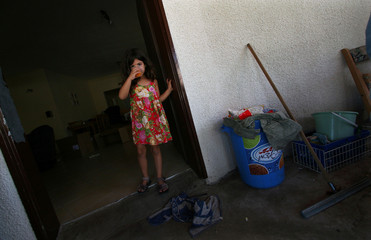 Girl stands by door with boxes in background at Elei Sinai settlement in Northern Gaza Strip.