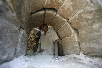 A worker stands inside a traditional oven at a cement processing factory in Samaria town