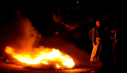 Residents of San Salvador Atenco stand guard at road block of burning tyres, at entrance to Atenco near Mexico City