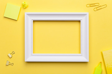 White Frame with Office Accessories on Yellow Background