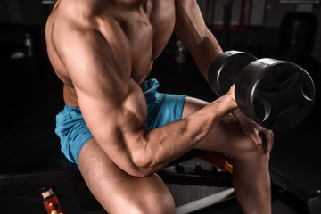 Very power athletic guy bodybuilder execute exercise with dumbbells at dark gym