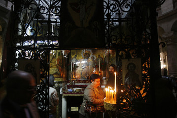 A worshipper lights a candle in the Church of the Holy Sepulchre in Jerusalem's Old City