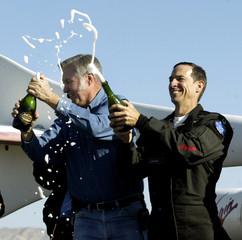 Burt Rutan and Brian Binnie pop champagne after SpaceShipOne wins X Prize.